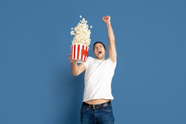Emotional watching cinema, flying popcorn. caucasian young man's portrait on blue studio background. male model in casual style, pastel colors. concept of human emotions, facial expression