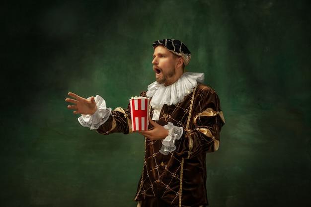 感情的なサッカー観戦。暗い背景の上に立っている古着の中世の若い男の肖像画。公爵、王子、王族としての男性モデル。時代、現代、ファッションの比較の概念。