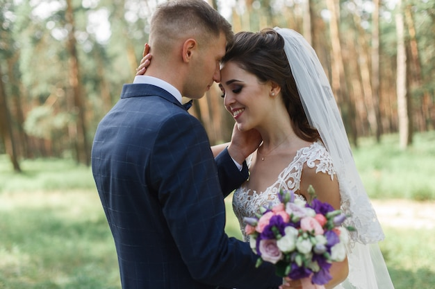 Emotional wedding couple in the  green park in spring. smiling bride and groom in sunny day outdoors. happy newlyweds hugging and kissing at the wedding day in nature.