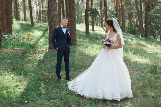 春の緑豊かな公園で感情的な結婚式のカップル。晴れた日の屋外で新郎新婦。晴れた日の自然の中で結婚式の日