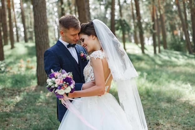 春の緑豊かな公園で感情的な結婚式のカップル。晴れた日の屋外で新郎新婦の笑顔。自然の中で結婚式の日にハグとキス幸せな新婚夫婦。