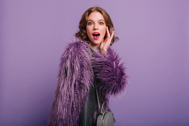 財布と紫色の背景にポーズをとってカラフルなメイクで感情的な白い女の子
