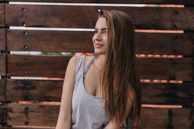 Emotiva donna bianca con i capelli lunghi in posa nella calda mattina di primavera. foto della meravigliosa ragazza caucasica isolata sulla parete di legno.