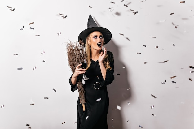Emotional witch in black hat drinking blood. glad female wizard holding goblet with potion.