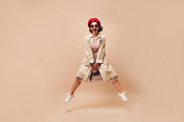 Donna emotiva in berretto e cappotto che salta su sfondo beige. ragazza luminosa con capelli scuri in occhiali da sole e scarpe da ginnastica bianche in posa.