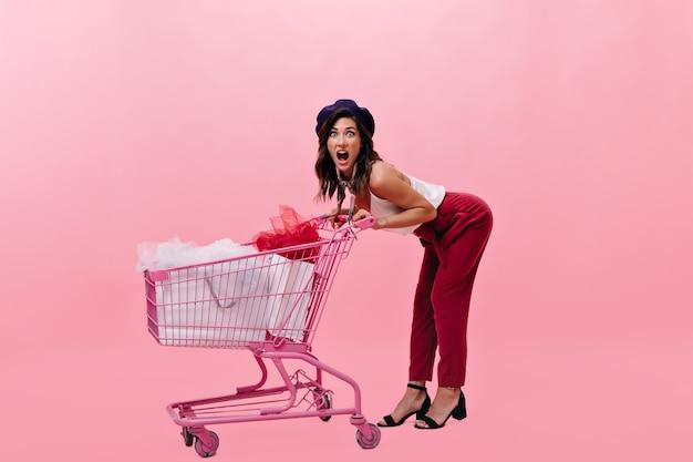 Donna emotiva in berretto in posa con il carrello della spesa rosa. ragazza in vestito moderno ed elegante che grida su priorità bassa isolata.