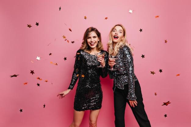Donna emotiva in pantaloni neri e giacca scintillante che beve vino. affascinanti amiche che godono della festa di compleanno.