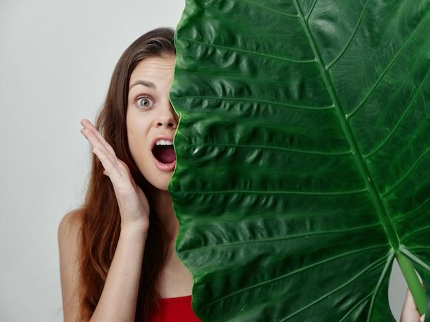 感情的な女性は彼女の顔の半分を緑の葉の赤い水着で覆います