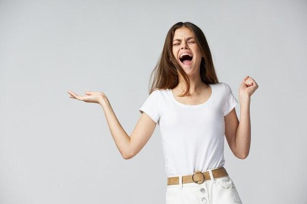 Эмоциональная женщина с закрытыми глазами с открытым ртом жест рукой образ жизни белая футболка