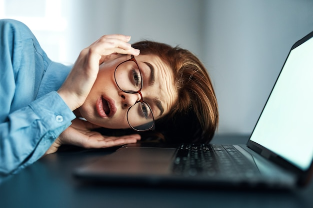 Emotional woman in front of laptop at night work disorder