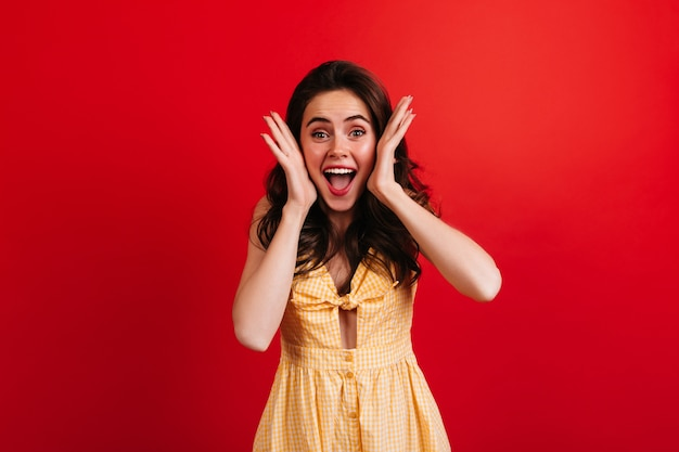 La donna emotiva grida felicemente sulla parete rossa. signora riccia in vestito a scacchi giallo in posa.