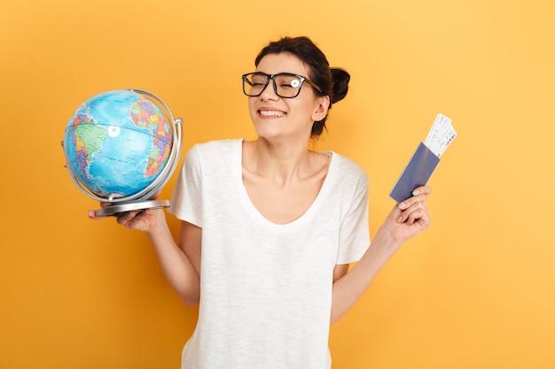 Эмоциональная женщина, держащая земной шар и паспорт с билетами.