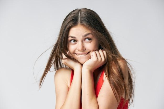 感情的な女性は、顔の魅力的な外観のライフスタイルのトリミングビューの近くに手を保持しています。