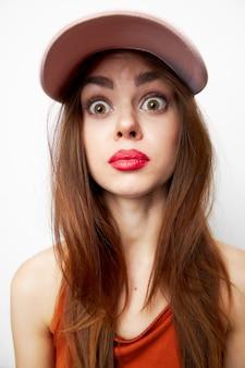 驚きの表情のおしゃれな服を着たキャップモデルの感情的な女性