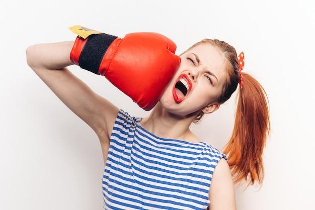 ボクシンググローブの赤い唇の縞模様のジャージのトレーニングで感情的な女性。高品質の写真