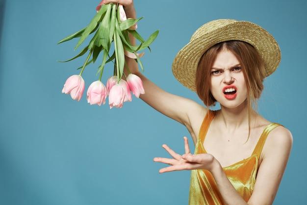 黄金のドレスと花の花束の感情的な女性