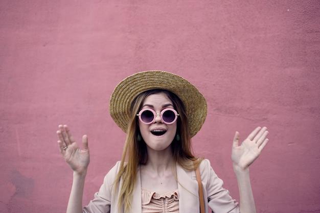 분홍색 벽 배경 도시 야외에서 걷는 모자에 감정적 인 여자. 고품질 사진