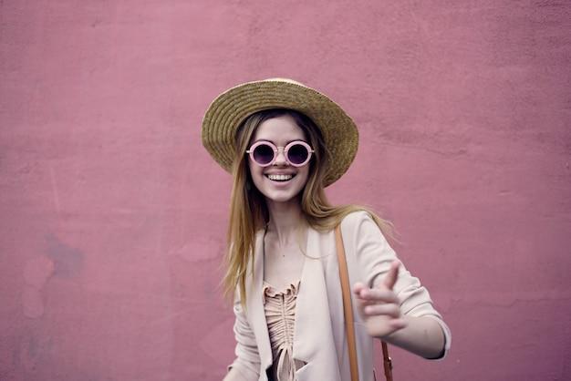 분홍색 벽 배경 도시 야외에서 걷는 모자에 감정적 인 여자.