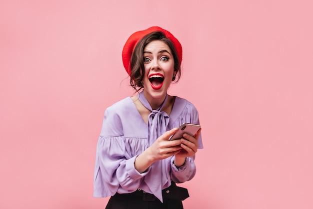 Эмоциональная женщина в красном берете и стильной рубашке с радостным удивлением смотрит в камеру и держит белый смартфон на розовом фоне.