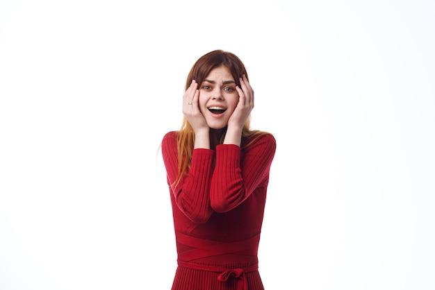 明るい背景の手で身振りで示す赤いドレスの感情的な女性。高品質の写真
