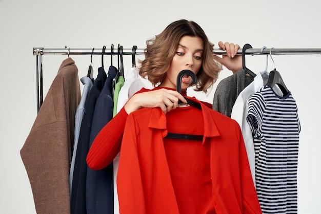상점 스튜디오 생활 방식에서 쇼핑하는 옷을 고르는 빨간 드레스를 입은 감정적인 여성