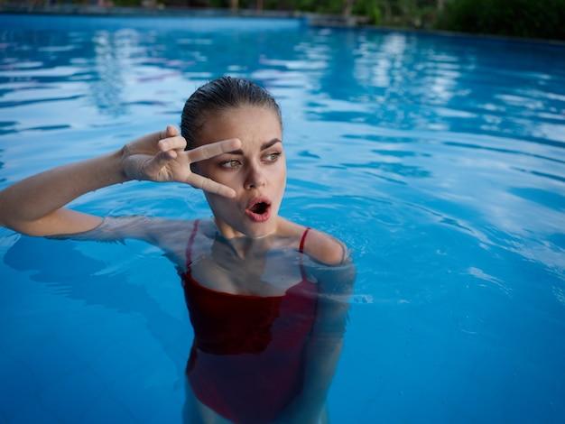 プールで赤い水着の感情的な女性は顔の近くに彼女の手を保持します Premium写真