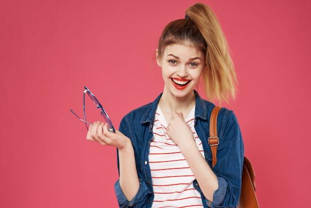 スタイリッシュな服のバックパックファッションピンクの背景の感情的な女性