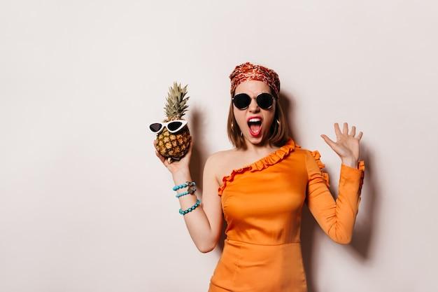 スタイリッシュなヘッドバンドとオレンジ色のドレスを着た感情的な女性は、大げさに叫び、サングラスでパイナップルを保持します。