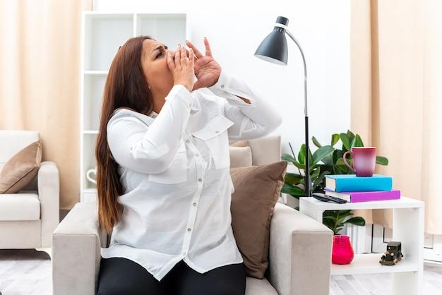 白いシャツと黒いズボンを着た感情的な女性が椅子に座り、明るいリビング ルームで口の近くに手を置いて叫ぶ