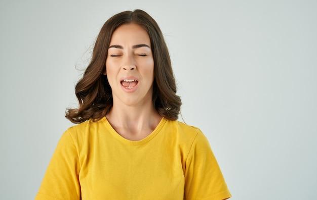 ヘアスタジオのトリミングされたビューを保持している黄色のtシャツの感情的な女性