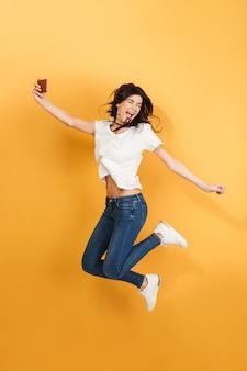 感情的な女性ジャンプは携帯電話でselfieを作ります。