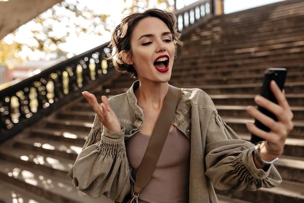 Donna emotiva in giacca oliva manica lunga che fa selfie fuori. cool donna con labbra rosse che cattura foto
