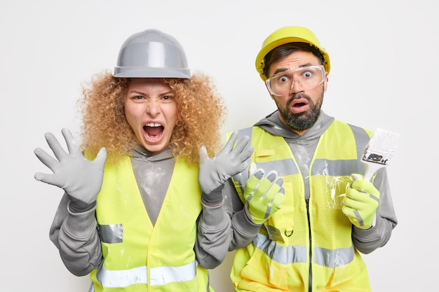 Emotional woman and man contractors get too much tasks wear protective helmets and safety uniform stand closely to each other react on something