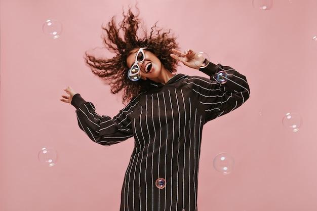 Donna emotiva in moderno abito nero e occhiali da sole che gioca con i suoi capelli ondulati, sorride e balla sul muro rosa isolato..