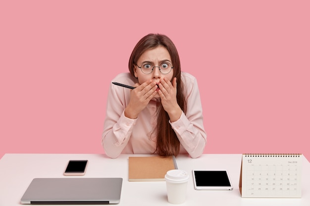 感情的な女性の完璧主義者は恐怖で見つめ、口に手を保ち、光学的な丸い眼鏡をかけ、仕事に最新の技術を使用しています