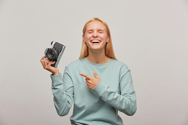 Emotional woman photographer laughing, holds a retro vintage photo camera in hand, pointing on it with finger