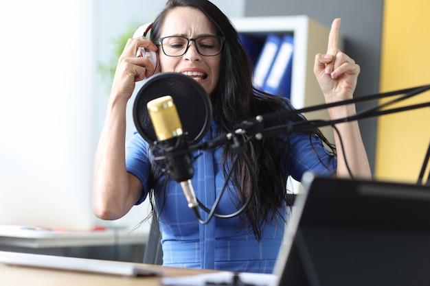 헤드폰을 끼고 있는 감정적인 여성 라디오 발표자는 마이크 음악 녹음 개념에 대해 이야기합니다.