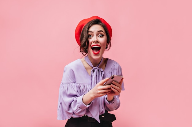 Emotional woman in red beret and stylish shirt in joyful surprise looks at camera and holds white smartphone on pink background.