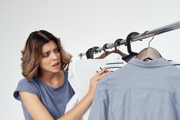 감정적 인 여성 쇼핑 중독자는 상점에서 쇼핑하는 옷을 선택합니다. 고립 된 배경