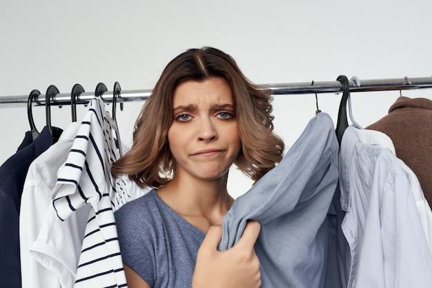 Эмоциональная женщина-шопоголик, выбирая одежду, делающую покупки в магазине светлом фоне