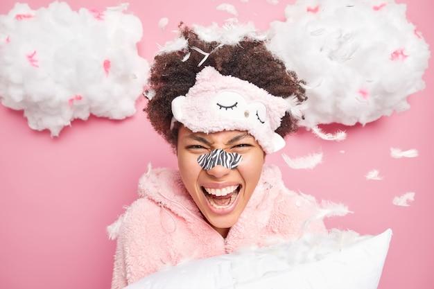 感情的な女性が大声で叫ぶパジャマに身を包んだ純粋な柔らかい肌に鼻パッチを適用し、飛んでいる羽の周りに枕のポーズを保持し、彼女の顔をきれいにします