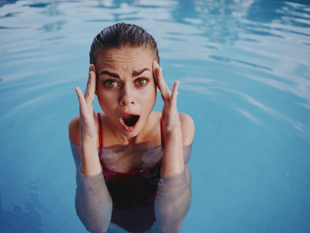 手で冷たい水でプールジェスチャーで泳ぐ感情的な女性