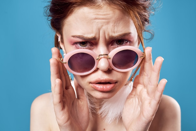 Эмоциональная женщина в темных круглых очках обнаженные плечи украшения крупным планом изолированный фон.