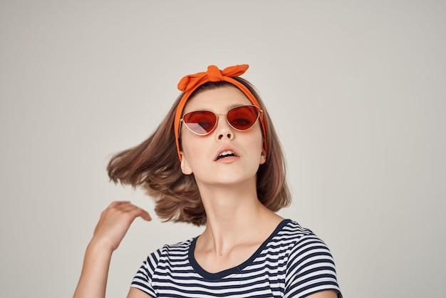 ストライプのtシャツのポーズのファッションでサングラスをかけている感情的な女性