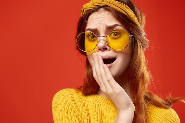 装飾をポーズの黄色いメガネファッションスタジオを身に着けている感情的な女性。高品質の写真