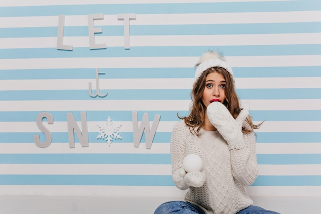 Emotional woman in white knitted hat over winter inscription: let it snow