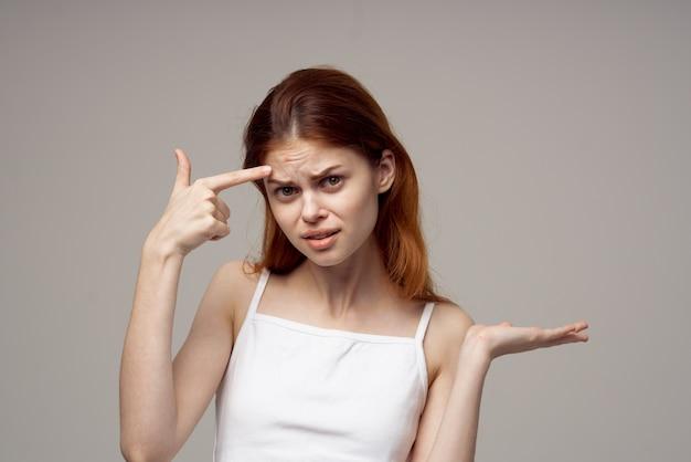 Эмоциональная женщина с прыщами на лице на сером фоне проблемы со здоровьем