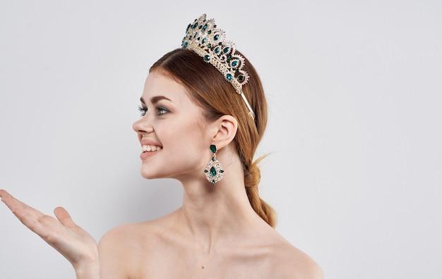 그녀의 머리와 아름다운 귀걸이 모델에 왕관과 함께 감정적 인 여자