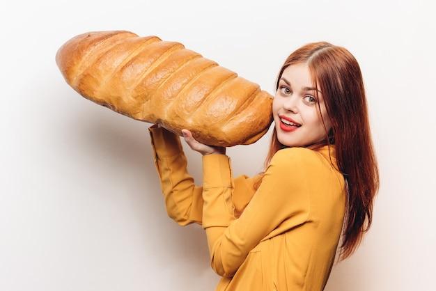 Эмоциональная женщина с огромным хлебом на светлом фоне забавный мучной продукт. фото высокого качества