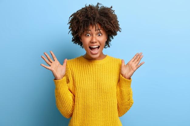 Donna emotiva con un afro in posa in un maglione rosa
